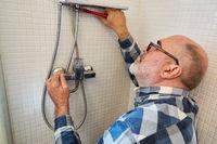 Klempner bei der Reparatur von Schlauch in der Dusche