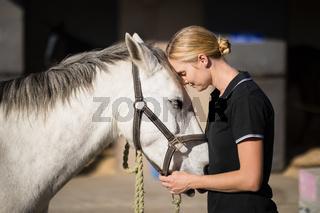female jockey loving horse at barn