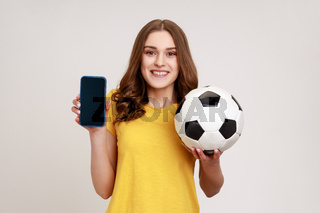 Smiling positive female of young age in yellow t-shirt holding and showing blank display smartphone and football ball, betting on soccer.