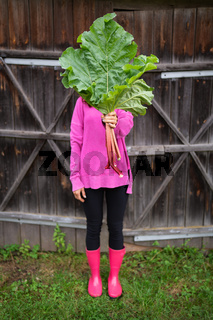 A woman in pink boots and a pink sweater holds a bouquet of rhubarb in her hands.
