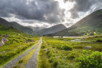 Straight country road leading trough Black Valley with dramatic sky, Ring of Kerry