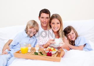 Smiling family having breakfast sitting on bed