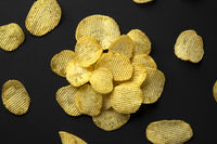 Ridged potato chips black background, top view