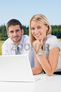 Business colleagues in nature with laptop smile