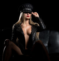 Sexy blonde topless in bdsm cap and leather jacket