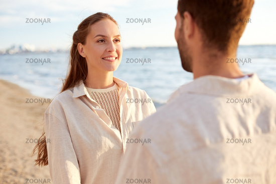 happy couple looking to each other on summer beach