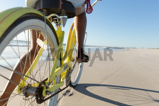 Low section of mixed race woman on beach holiday riding bicycle on the sand by the sea
