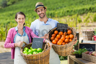 Portrait of smiling couple holding fresh fruits in wicker baskets