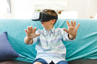 Caucasian boy sitting on couch and using vr headset in living room