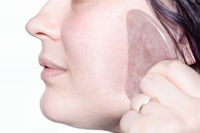 woman massages cheek with quartz scraper close up