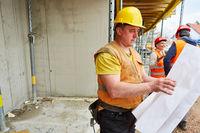 Vorarbeiter mit Bauzeichnung und Arbeiter Team
