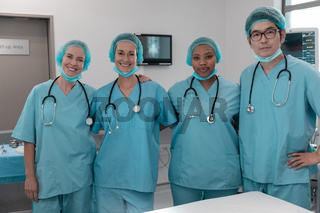 Portrait of diverse group of male and female doctors standing in operating theatre