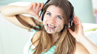 Cheerful caucasian girl listening to music sitting on a sofa