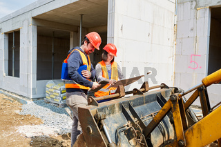 Architektin und Handwerker schauen auf Bauplan