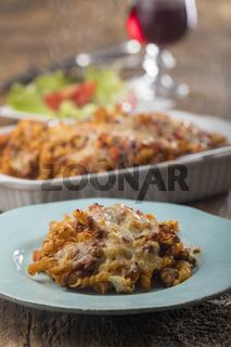 überbackene Pasta mit Salat auf Holz