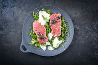 Modern style traditional fried New York strip steak with rucola and parmesan offered as top view on a design plate