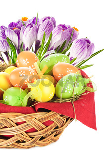 Painted easter eggs in basket and spring flowers