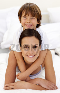 Son hugging his mother in bed