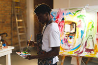 African american male painter at work holding paints and brush in art studio
