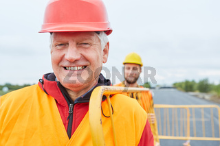 Bauarbeiter und Kollege tragen Absperrgitter