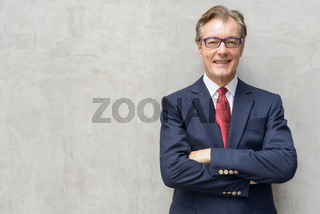 Handsome mature businessman smiling with arms crossed
