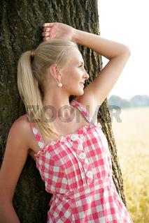 junge Frau lehnt an einem Baum
