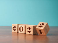 Flipping wooden cubes with the Year number 2021 and 2022, New Year concept