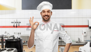 happy smiling male chef showing ok at kitchen