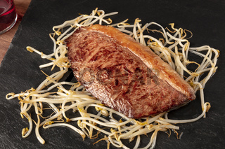 Kobe meat, wagyu beef steak, seared, with soy sprouts, on black