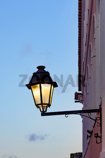 Old metal lanterns on the wall of a colonial house with the sky in the background during nightfall