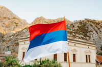 The flag of Serbia flies against the backdrop of a building and mountains on a sunny day.
