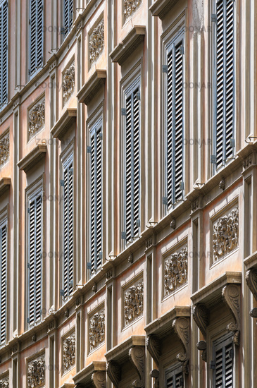Vintage rainessance house with window shutters in summer in medieval Trastevere district of Rome, Italy