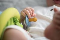 hand of baby holding pacifier