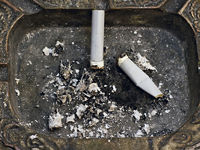 two cigarette butts in the ashtray in the backgrou