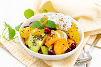 Salad fruit with cranberries and cream in bowl on board