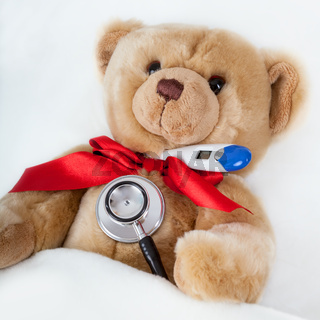 Teddy is with clinical thermometer in bed