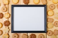 Composition of white card in frame with copy space and christmas cookies on wooden background