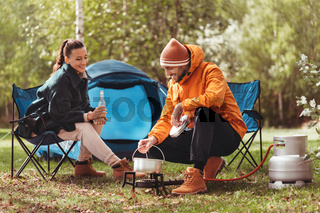 couple drinking beer and cooking food at tent camp