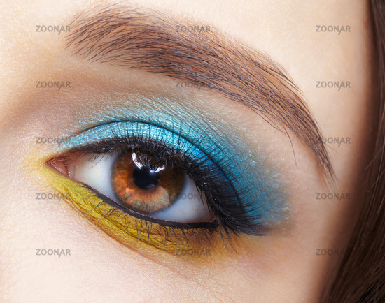 Human female eye with blue smoky eyes shadows and yellow liner.