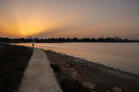 A woman walks at sunset along a footpath on Larnaca salt lake shore with the Hala Sultan Tekke mosque in the background