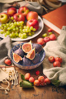 Dish with figs, apples and grapes with warm cozy knitwear, autumn leaves and apples.