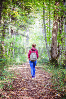 Get your mind free and forest therapy concept: Young girl is hiking through the green forest