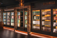 Variety of Bushmills whiskey in a rows on illuminated shelfs on a display in distillery visitor centre and shop