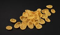 Corn flakes on black background, top view