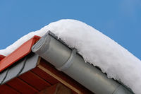 Roof with snow on a sunny day with blue sky as background