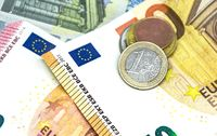 One euro coin over some banknotes of different values