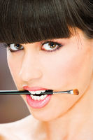 woman hold make up brush between teeth