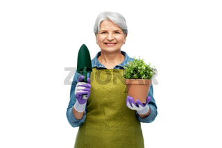 old woman in garden apron with flower and trowel