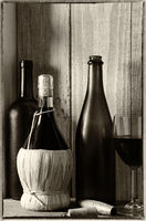 Black and Wite vintage wine still life with warm light from a window on the side. Three bottles, a w