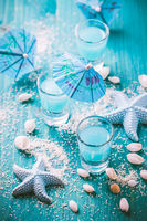 Blue shots for summer with seashells on blue background. Small alcoholic cocktails.